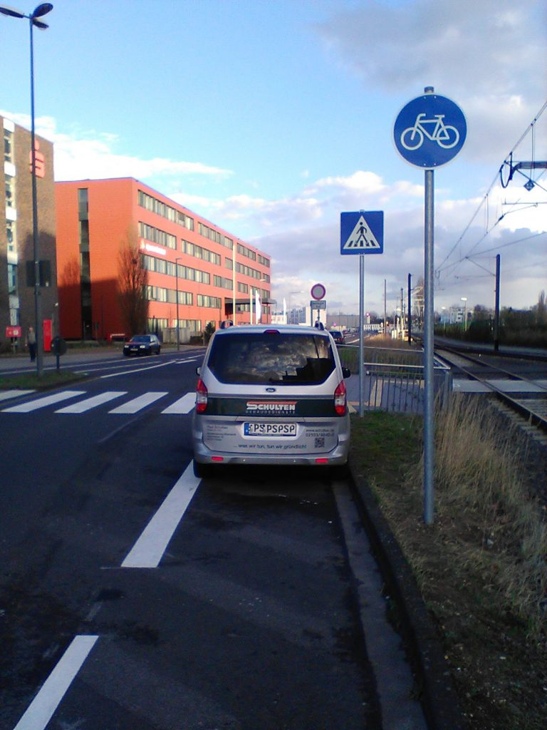 gründliches Falschparken par Excellence: Ein Auto parkt auf dem Radweg direkt vor dem Zebrastreifen.